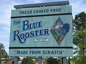 "The Blue Rooster sign. Text: ""Fresh Cooked Food,"" est 2012, ""Made from Scratch."""