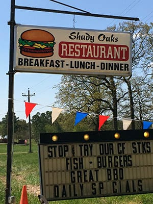 Shady Oaks Restaurant sign. Text: Breakfast, Lunch, Dinner, Stop and try our CF Stks, fish, burgers, Great BBQ, Daily Specials.